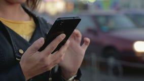 Portret van een jong meisje dat zich in de stad, in haar handen een smartphone, mobiele telefoon bevindt stock footage