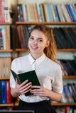 Portret van een jong meisje, met een boek in de bibliotheek stock foto's