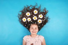 Portret van een jong meisje met madeliefjes in hun haar die op de vloer liggen royalty-vrije stock foto's
