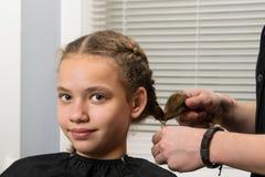 Portret van een jong meisje, op het tijdstip van het vlechten van vlechten stilist-merk-omhooggaande kunstenaar stock afbeeldingen