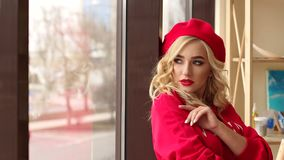 Portret van een jong meisje in een rode kleding en hoed dichtbij het venster Art stock video