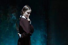 Portret van een jong meisje in school eenvormig als moordenaarsvrouw stock foto