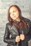 Portret van een jong meisje zonder make-up op haar gezicht in een zwart jasje tegen een grijze bakstenen muur stock fotografie