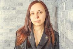 Portret van een jong meisje zonder make-up op haar gezicht in een zwart jasje tegen een grijze bakstenen muur royalty-vrije stock fotografie