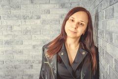 Portret van een jong meisje zonder make-up op haar gezicht in een zwart jasje tegen een grijze bakstenen muur stock foto's