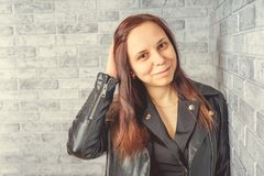 Portret van een jong meisje zonder make-up op haar gezicht in een zwart jasje tegen een grijze bakstenen muur royalty-vrije stock foto