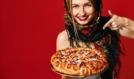 Portret van een jong mooi blonde in headscarf die een heerlijke eigengemaakte bessenpastei houden royalty-vrije stock afbeelding