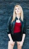 Portret van een jong mooi blondemeisje in een zwart jasje en borrels die dichtbij bakstenen muur stellen Royalty-vrije Stock Afbeeldingen