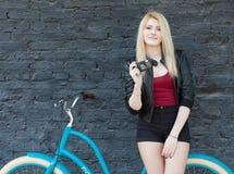 Portret van een jong mooi blondemeisje in een zwart jasje en borrels die dichtbij de bakstenen muur naast helder blauw uitstekend Stock Fotografie