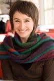 Portret van een jong mooi brunette in een gestreepte sjaal Royalty-vrije Stock Foto