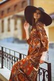 Portret van een jong mooi meisje in een kleding in de stad Stock Foto