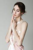 Portret van een jong mooi meisje in een lichtrose kleding in de studio op een grijze achtergrond Stock Afbeeldingen