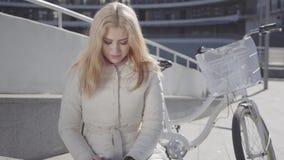 Portret van een jong mooi meisje met blond haar en in een lichte jasjezitting op een bank naast de fiets Het meisje stock video