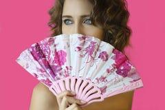 Portret van een jong mooi meisje met heldere samenstelling en een ventilator in handenclose-up op een roze achtergrond Stock Afbeelding