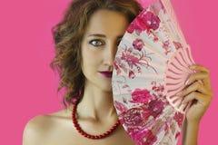 Portret van een jong mooi meisje met heldere samenstelling en een ventilator in handenclose-up op een roze achtergrond Royalty-vrije Stock Foto's