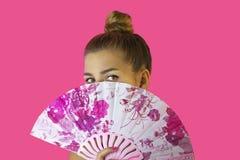 Portret van een jong mooi meisje met heldere samenstelling en een ventilator in handenclose-up op een roze achtergrond Royalty-vrije Stock Afbeeldingen