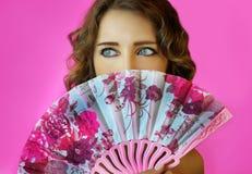 Portret van een jong mooi meisje met heldere samenstelling en een ventilator in handenclose-up op een roze achtergrond Stock Afbeeldingen