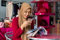 Portret van een jong moslim van de ondernemerszitting en lezing tijdschrift die nieuwe voorraadcatalogus in haar manierboutique k stock foto's