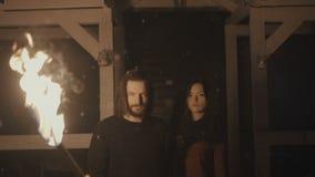 Portret van een jong mysticuspaar die een toorts in dark houden stock video