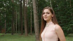 Portret van een jong vrouwenmodel in een goede stemming die zich in park, het onderzoeken van camera en het glimlachen bevinden stock video