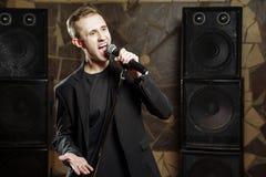 Portret van een jonge aantrekkelijke mens die met een microfoon zingen stock afbeelding