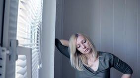 Portret van een jonge aantrekkelijke mooie blonde zich dichtbij het venster bevindt en vrouw die in camera kijkt stock videobeelden