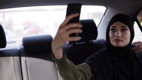 Portret van een jonge, aantrekkelijke moslimvrouw die hijab het omzetten in een auto dragen Zij draagt dark kleedt zich, het zitt stock footage