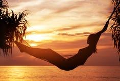 Portret van een jonge, aantrekkelijke vrouw die op een zonsondergang letten stock foto