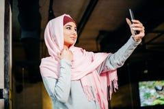 Portret van een jonge aantrekkelijke vrouw in hijab die selfie foto op smartphone maken stock foto's