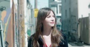 Portret van een jonge, aantrekkelijke vrouw in een stedelijk stadsmilieu stock video
