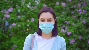 Portret van een jonge allergische vrouw die een medisch masker dragen stock videobeelden