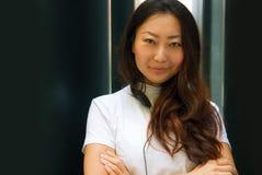Portret van een jonge Aziatische vrouw die in wit met hoofdtelefoons aan muziek met haar smartphone luisteren stock foto