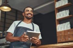 Portret van een jonge bedrijfseigenaar in zijn koffie stock foto