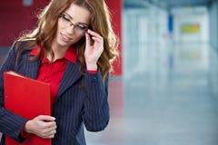 Portret van een jonge bedrijfsvrouw die, in bureauen glimlachen Stock Foto's