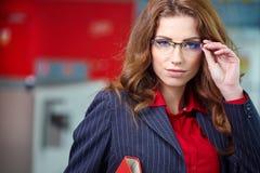 Portret van een jonge bedrijfsvrouw die, in bureauen glimlachen Royalty-vrije Stock Afbeelding