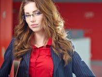 Portret van een jonge bedrijfsvrouw die, in bureauen glimlachen Royalty-vrije Stock Fotografie