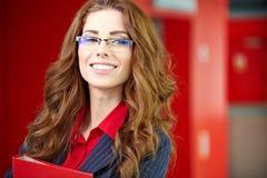 Portret van een jonge bedrijfsvrouw die, in bureauen glimlachen Stock Afbeeldingen