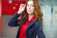 Portret van een jonge bedrijfsvrouw die, in bureauen glimlachen Stock Fotografie