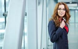 Portret van een jonge bedrijfsvrouw die, in bureauen glimlachen Royalty-vrije Stock Foto's