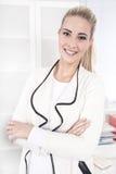 Portret van een jonge blonde het glimlachen gevouwen onderneemsterwapens Stock Foto's