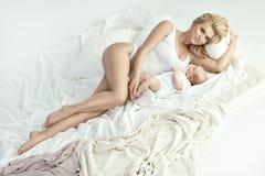 Portret van een jonge blonde moeder met een pasgeboren baby Stock Fotografie