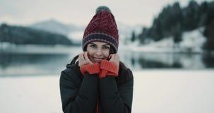 Portret van een jonge dame die recht aan camera groot glimlachen heeft zij een wit vastbindt, dame die een rode hoed dragen kijke stock videobeelden