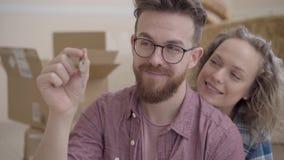 Portret van een jonge die familie naar een nieuw huis wordt verplaatst Gebaarde mens met glazen die de sleutels tonen aan een nie stock video