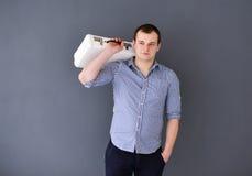 Portret van een jonge die mens met schouderzak op grijze achtergrond wordt geïsoleerd stock foto