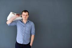 Portret van een jonge die mens met schouderzak op grijze achtergrond wordt geïsoleerd royalty-vrije stock foto's