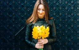 Portret van een jonge donkerbruine vrouw die gele de lentebloemen houden stock foto