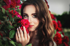 Portret van een jonge donkerbruine vrouw op een achtergrond van rozen Stock Foto's