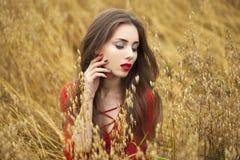 Portret van een jonge donkerbruine vrouw in rode kleding Stock Afbeeldingen