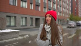 Portret van een jonge droevige mooie vrouw, een meisje die in koud weer in regenachtige dag bij stadsstraat in openlucht lopen, d stock video