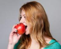 Portret van een jonge gemberdame in turkooise blouse met een appl Royalty-vrije Stock Foto's